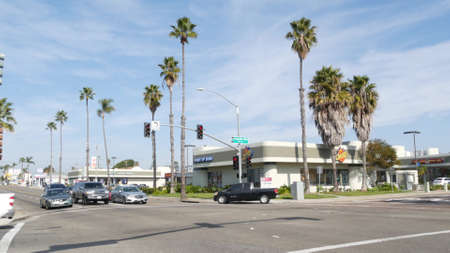 Oceanside, California USA - 27 Jan 2020: Palm trees on Route 101 american highway, pacific coast tropical street. Traffic light and auto transport on road intersection, cars on crossroad in suburb.
