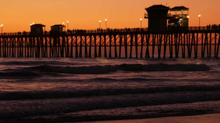 Oceanside, California USA - 16 Feb 2020: Surfer silhouette, pacific ocean beach in evening, water waves and sunset. Tropical coastline, waterfront vacation resort. People enjoy surfing as sport hobby. Standard-Bild - 158644887
