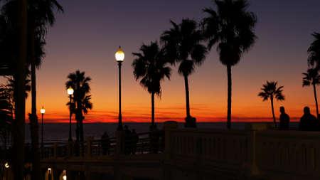 Oceanside, California USA - 27 Dec 2020: Palms silhouette twilight sky, dusk nightfall atmosphere. People walking on pier. Tropical pacific ocean beach, sunset afterglow aesthetic. Los Angeles vibes. Standard-Bild - 158644890