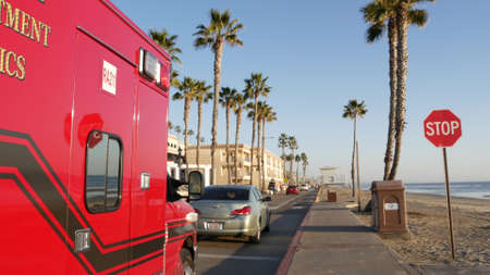 Oceanside, California USA - 11 Feb 2020: EMS emergency medical service red vehicle by ocean beach. Fire department ambulance car. Lifeguard paramedic rescue truck on beachfront road. 911 public safety