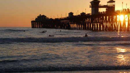 Oceanside, California USA - 16 Feb 2020: Surfer silhouette, pacific ocean beach in evening, water waves and sunset. Tropical coastline, waterfront vacation resort. People enjoy surfing as sport hobby. Standard-Bild - 158644894