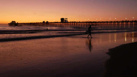 Oceanside, California USA - 16 Feb 2020: Surfer silhouette, pacific ocean beach in evening, water waves and sunset. Tropical coastline, waterfront vacation resort. People enjoy surfing as sport hobby.