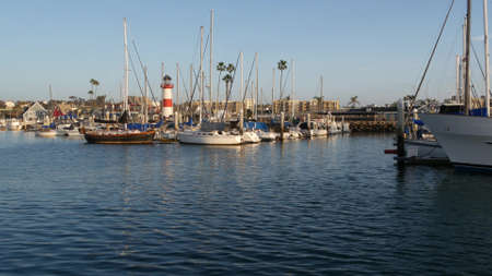Oceanside, California USA - 27 Jan 2020: Waterfront harbor fisherman village, yachts sailboats floating, marina harbor quay. Sail boat masts, nautical vessels moored in port, lighthouse or beacon.