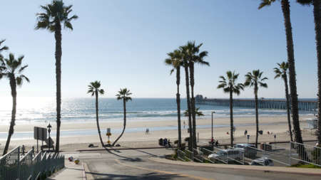 Oceanside, California USA - 8 Feb 2020: People walking strolling, waterfront resort street, pacific ocean tropical beach with palm trees. Person riding bicycle, coastal road perspective. Biker cycling Standard-Bild - 158644899