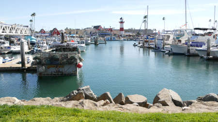 Oceanside, California USA - 26 Feb 2020: Harbor village with fisherman boats and yachts, pacific ocean coast marina, sea shore. Nautical vessel for fishing in port, fishery industry. Lighthouse beacon Standard-Bild - 158644898