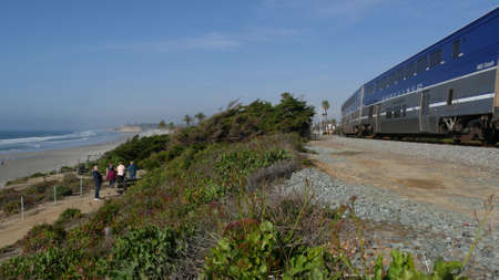 Del Mar, California USA - 23 Jan 2020: Pacific surfliner train, travel ocean beach. Passenger railroad, public transit. Express rapid intercity double decker blue commuter. Amtrak railway transport.