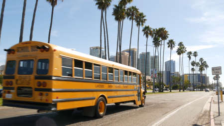 San Diego, California USA - 31 Jan 2020: American yellow school bus on street in downtown. Schoolbus shuttle on road, city near Los Angeles. Education transportation infrastructure. Civic Center. Editorial