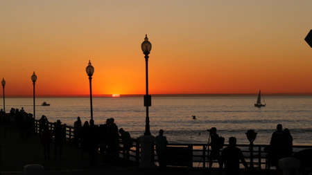 Oceanside, California USA - 17 Nov. 2019: Wooden pier and people walking. Tourists strolling in waterfront resort, summertime vacations near Los Angeles. Sunset ocean beach, tropical sunny orange sky. Standard-Bild - 158644911