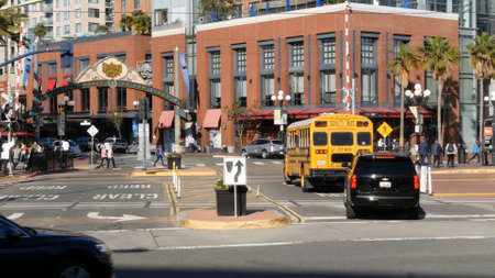 San Diego, California USA - 13 Feb 2020: American yellow school bus on street in downtown. Schoolbus shuttle on road, city near Los Angeles. Education transportation infrastructure. Gaslamp arch sign. Editorial