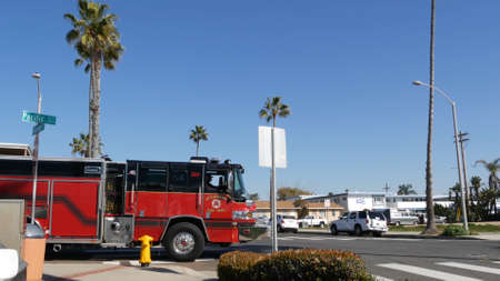 Oceanside, California USA - 8 Feb 2020: Red fire engine on street of city near Los Angeles. Firefighters vehicle or truck, american Fire Department car. 911 public safety. Firetruck and yellow hydrant