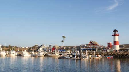 Oceanside, California USA - 27 Jan 2020: Waterfront harbor fisherman village, yachts sailboats floating, marina harbor quay. Sail boat masts, nautical vessels moored in port, lighthouse or beacon. Standard-Bild - 159003935