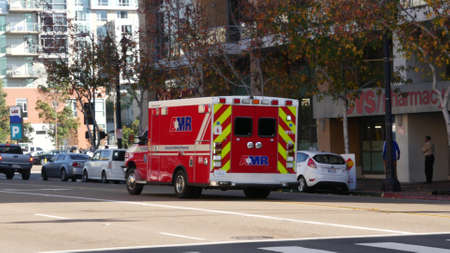 San Diego, California USA - Jan 4, 2020: AMR american medical response ambulance car. EMS emergency service red vehicle, downtown city street. Paramedic rescue truck. 911 public safety. Man on scooter. Editorial