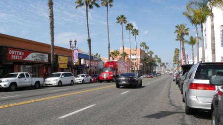 Oceanside, California USA - 20 Feb 2020: Coca Cola truck, red lorry on Pacific Coast Highway 1, historic route 101. Palm trees on street, road along ocean. Cocacola caravan in city near Los Angeles.