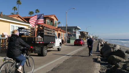 Oceanside, California USA - 16 Feb 2020: People walking strolling on waterfront sea promenade, beachfront boardwalk. Vacations ocean beach resort near Los Angeles. Riding bike bicycle, US flag on car. Standard-Bild - 159003833