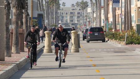 Oceanside, California USA - 8 Feb 2020: People walking on waterfront promenade, beachfront boardwalk near pier. Vacations ocean beach resort near Los Angeles. Biker riding bicycle, two men cycling.