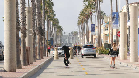 Oceanside, California USA - 8 Feb 2020: People on waterfront promenade, beachfront boardwalk near pier. Vacations ocean beach resort near Los Angeles. Man and woman skateboarding, teens on skates. Editorial