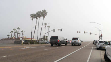 Encinitas, California USA -20 Feb 2020: Traffic light semaphore on highway 101 road by misty beach. Fog on sea shore, pacific ocean coast. Freeway with cars along shoreline, coastline near Los Angeles