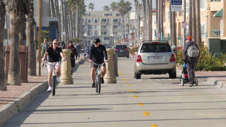 Oceanside, California USA - 8 Feb 2020: People walking on waterfront promenade, beachfront boardwalk near pier. Vacations ocean beach resort near Los Angeles. Biker riding bicycle, two men cycling.