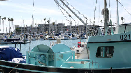 Oceanside, California USA - 26 Feb 2020: Harbor village with fisherman boats and yachts, pacific ocean coast marina, sea shore. Blue nautical vessel for fishing in port, fishery industry. Quay in bay.