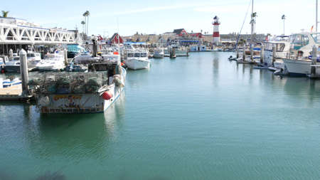 Oceanside, California USA - 26 Feb 2020: Harbor village with fisherman boats and yachts, pacific ocean coast marina, sea shore. Nautical vessel for fishing in port, fishery industry. Lighthouse beacon Standard-Bild - 159003852