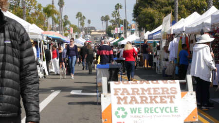 Oceanside, California USA -20 Feb 2020 People walking on marketplace, customer on farmers market. Vendors sell to byers locally produced goods. Street trading stalls and tents. We recycle plastic free