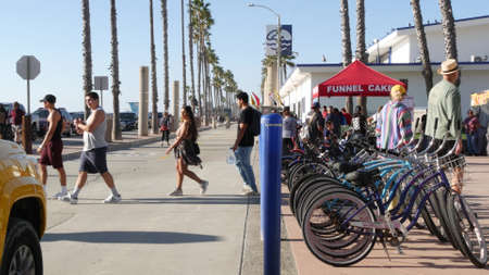 Oceanside, California USA -16 Feb 2020: People walking strolling, waterfront sea promenade, beachfront boardwalk near pier. Vacations ocean beach resort near Los Angeles. Lifeguard car, bike bicycle. Editorial