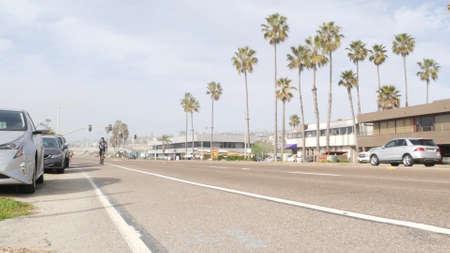 Encinitas, California USA -20 Feb 2020: Traffic light semaphore on highway 101 road by misty beach. Fog on sea shore, pacific ocean coast. Freeway with cars along shoreline coastline. Biker on bicycle