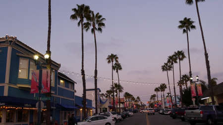 Oceanside, California USA - 18 Feb 2020: Pier View Coffee cafe. Palm trees in twilight, typical american street, pacific coast tropical beach resort. Cars parked on road, generic view of evening city.