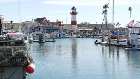 Oceanside, California USA - 26 Feb 2020: Harbor village with fisherman boats and yachts, pacific ocean coast marina, sea shore. Nautical vessel for fishing in port, fishery industry. Lighthouse beacon