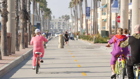 Oceanside, California USA - 8 Feb 2020: People walking on waterfront promenade, beachfront boardwalk near pier. Vacations ocean beach resort near Los Angeles. People in pajama riding bikes or bicycles