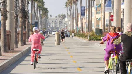 Oceanside, California USA - 8 Feb 2020: People walking on waterfront promenade, beachfront boardwalk near pier. Vacations ocean beach resort near Los Angeles. People in pajama riding bikes or bicycles Standard-Bild - 159003861