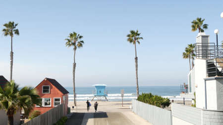 Oceanside, California USA - 20 Feb 2020: Surfer man with surfboard going surfing ocean waves. Colorful waterfront cottages and lifeguard tower, watchtower. Multicolor bungalow huts by sea. Palm trees. Editorial