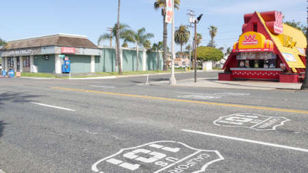 Oceanside, California USA - 20 Feb 2020: Wienerschnitzel hot dog fast food, pacific coast highway, historic route 101. Palm trees on street, road along ocean. FedEx delivery van, Federal Express truck