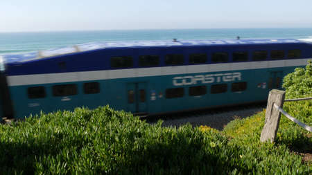 Del Mar, California USA - 23 Jan 2020: Coaster train, travel along pacific ocean beach. Passenger railroad, public transit. Express rapid intercity double decker blue commuter. NCTD railway transport.