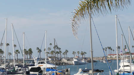 Oceanside, California USA - 27 Jan 2020: Waterfront harbor fisherman village, luxury yachts sailboats floating, marina harbour quay. Sail boat masts, nautical vessels anchored or moored in port.