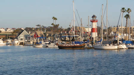 Oceanside, California USA - 27 Jan 2020: Waterfront harbor fisherman village, yachts sailboats floating, marina harbour quay. Sail boat masts, nautical vessels moored in port, lighthouse or beacon.