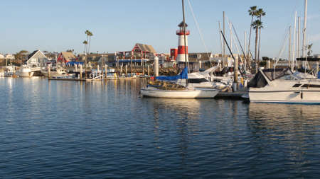 Oceanside, California USA - 27 Jan 2020: Waterfront harbor fisherman village, yachts sailboats floating, marina harbour quay. Sail boat masts, nautical vessels moored in port, lighthouse or beacon. Standard-Bild - 161603733