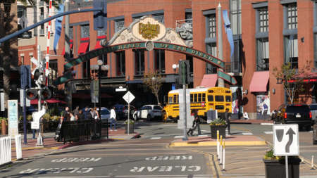 San Diego, California USA - 13 Feb 2020: American yellow school bus, street in downtown. Schoolbus shuttle on road, city near Los Angeles. Education transportation infrastructure. Gaslamp Quarter sign