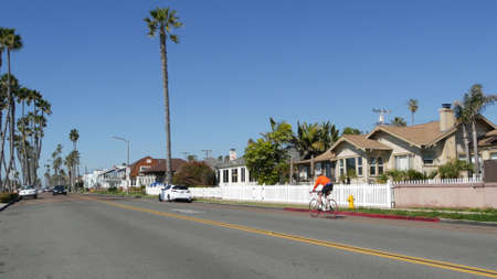 Oceanside, California USA - 8 Feb 2020: Person riding bicycle on road, tropical beach palm trees. Biker cycling bike, healthy lifestyle sport hobby. People on waterfront Pacific street, coastal suburb Standard-Bild - 161603760