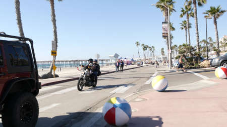 Oceanside, California USA - 8 Feb 2020: People walking, waterfront promenade near pier, pacific ocean tropical beach tourist resort and palm trees. Couple on motorcycle, beachfront street on sunny day