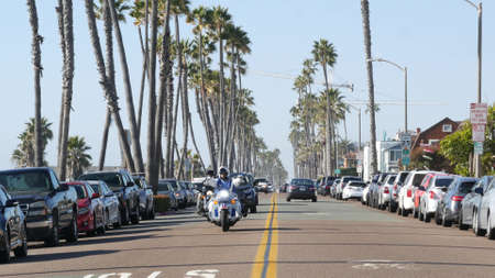 Oceanside, California USA - 16 Feb 2020: Cars and biker men on motorbikes, waterfront road. Pacific ocean tropical beach tourist resort with palm trees. Beachfront street on sunny summer day.