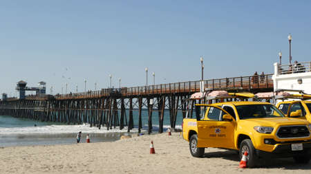 Oceanside, California USA - 8 Feb 2020: Yellow lifeguard car, beach near Los Angeles. Coastline rescue, life guard Toyota pick up truck, lifesavers vehicle. Iconic auto on ocean coast. Public safety.