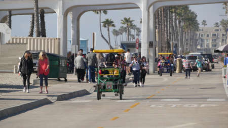 Oceanside, California USA - 8 Feb 2020: People walking on waterfront promenade, beachfront boardwalk. Vacations ocean beach resort near Los Angeles. Family riding surrey 4 wheel double bench bike.