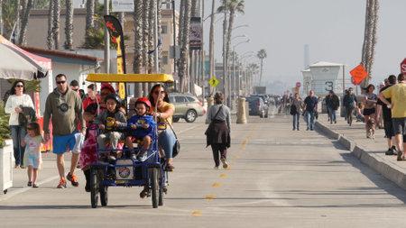 Oceanside, California USA - 8 Feb 2020: People walking on waterfront promenade, beachfront boardwalk. Vacations ocean beach resort near Los Angeles. Family riding surrey 4 wheel double bench bike. Standard-Bild - 161603750