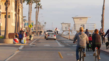 Oceanside, California USA - 8 Feb 2020: People walking, waterfront promenade, beachfront boardwalk near pier. Vacations ocean beach resort near Los Angeles. Biker riding bicycle. Man and woman cycling
