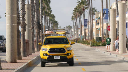 Oceanside, California USA - 8 Feb 2020: People walking on waterfront promenade, beachfront boardwalk near pier. Vacations ocean beach resort near Los Angeles. Yellow lifeguard Toyota car pick up truck Editorial