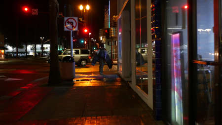 Oceanside, California USA - 9 Feb 2020: Lonely man looks like homeless walking, city street walkway at night. Male person on sidewalk, possible unemployed jobless beggar. Poverty and begging problem.