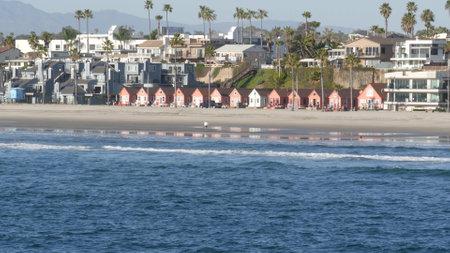Oceanside, California USA - 11 Feb 2020: Local people walking strolling, pacific ocean coast, beach from pier. Sea water waves tide, shore sand. Beachfront vacations resort. Waterfront promenade.