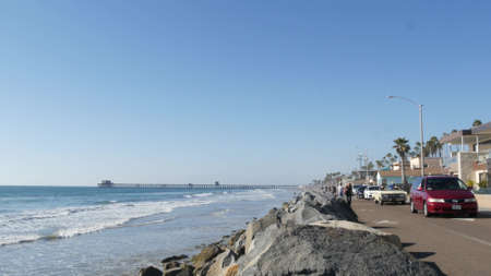 Oceanside, California USA -16 Feb 2020: People walking strolling on waterfront sea promenade, beachfront boardwalk near pier. Vacations ocean beach resort near Los Angeles. Vintage retro cabriolet car