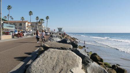 Oceanside, California USA - 16 Feb 2020: People walking strolling on waterfront sea promenade, beachfront boardwalk near pier. Vacations ocean beach resort near Los Angeles. Surrey bike bicycle riding